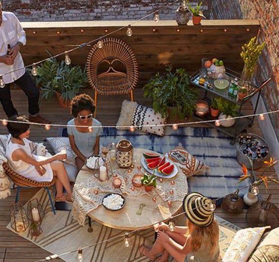 dachterrasse mit holzgeländer kreativ gestalten als cafe mit gemusterten Teppichen, Sitzkissen um rundem Kaffeetisch aus holz, lichterkette mit glühbirnen und beistelltisch auf rollen