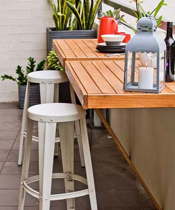 coole gestaltungsidee für kleine terrassen mit zwei klapptischen aus holz, weißen runden hockern und grauen rechteckigen blumenkübeln