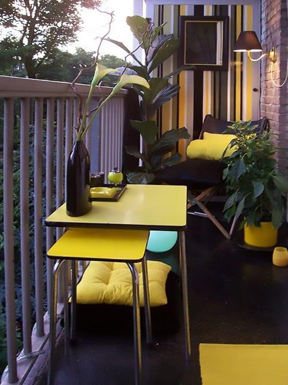 terrasse einrichten mit klappsessel schwarz, kleinem Tisch mit hocker in gelb, gelben kissen und blumentöpfen und wand dekorieren mit tapeten und wandlampe