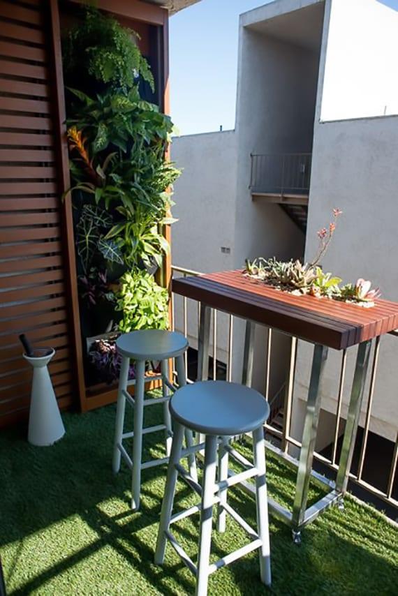 kleine terrasse modern gestalten mit wandverkleidung aus holzlatten und pflanzen und beweglichem Kaffetisch auf rollen