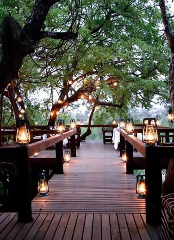 romantische terrassengestaltung einer holzterrasse zwischen bäumen mit gaslampen