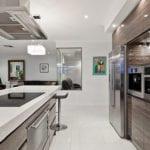 moderne küche mit weißem bodenbelag, eingebauten haushaltsgäreten und kochinsel mit weißer arbeitsküchenplatte
