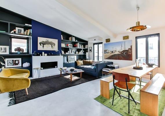schickes wohn-esszimmer design mit weißem bodenbelag, blauem sofa und gelbem sessel auf schwarzem teppich, schwarze Akzentwand mit modernem kamin und wandnischen mit einbauregalen