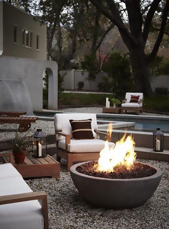 coole gartengestaltung mit kies, holzgartenmöbel mit weißen polstern und rundem betonkamin