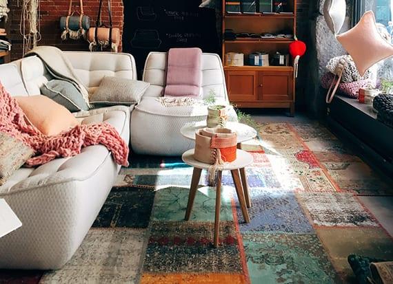 Bunte Wohnzimmergestaltung Mit Gemusterten Teppichfliesen, Designer  Polstersofa Weiß Und Schaufenster Deko Mit Hängenden Kissen