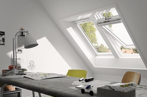schickes homeoffice in dachwohnung mit weißen dachfenstern, modernem arbeitstisch grau mit weißem tischlampe und grünem stuhl