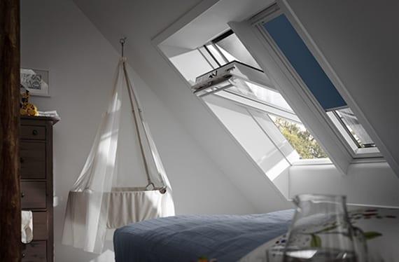 schlafzimmer mit dachschräge wohnlich einrichten mit blauen fensterrollläden, rustikaler kommode und hängende babyschaukel in weiß