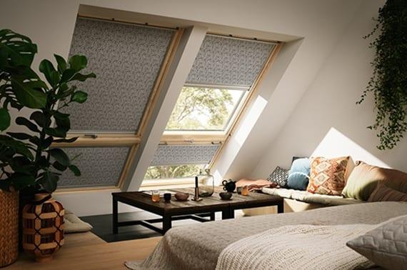 coole einrichtungsidee für gemütliches schlafzimmer mit, parkett, pflanzen, sofa mit couchtisch aus metall und holz vor dachfenster mit holzfensterrahmen und grauen fensterrollläden