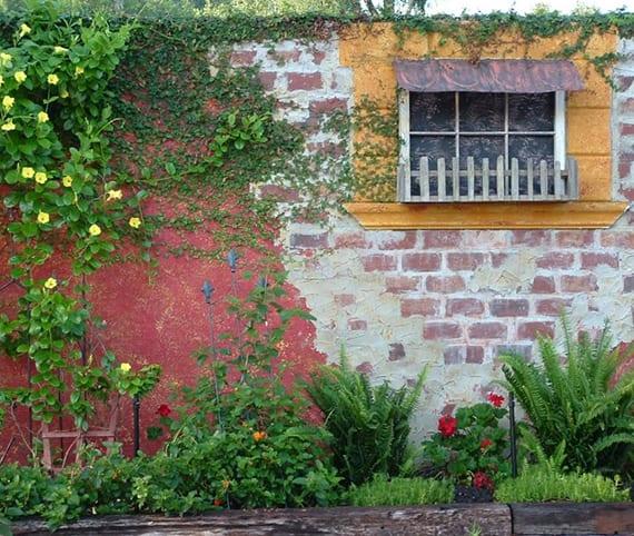 authentische gartenmauer aus ziegeln und rotem putz als gestaltungselement im garten