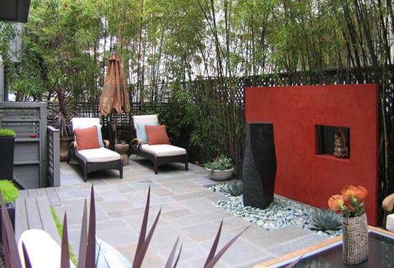 stilvolle gartengestaltung mit roter akzentwand, dekorativem wassespiel aus schwarzem basalt unf grüne pflanzen in hohen blumenkübeln schwarz