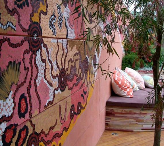 coole gartenideen für hofgarten gestaltung mit holzbodenbelag, gerundeter sitzecke mit kissen und polster und tolle wandgestaltung mit punkt-malerei