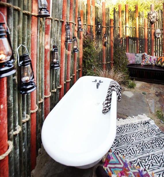 coole gartengestaltung mit gartenzaun aus schwarzen und roten metallröhren mit ausgehängten gaslampen und masken, sitzecke mit freistenede badewanne und gemusterten textilien