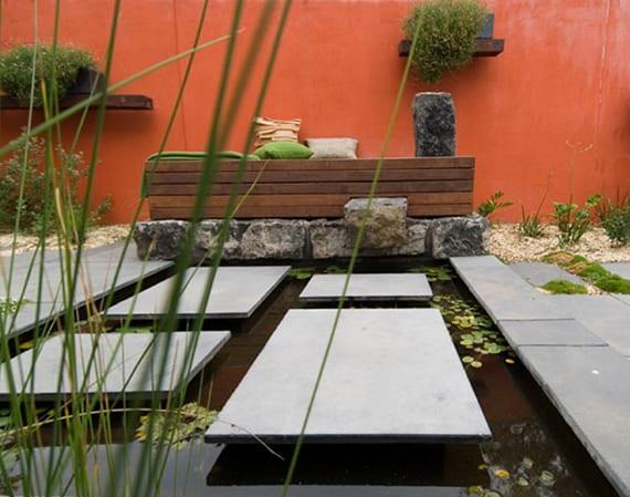 moderne gartengestaltung mit roter gartenmauer, wasserbecken mit steinplatten und holzbank auf stein