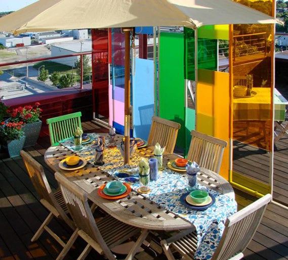 bunte terrassengestaltung mit trennwand aus farbigem plexiglas