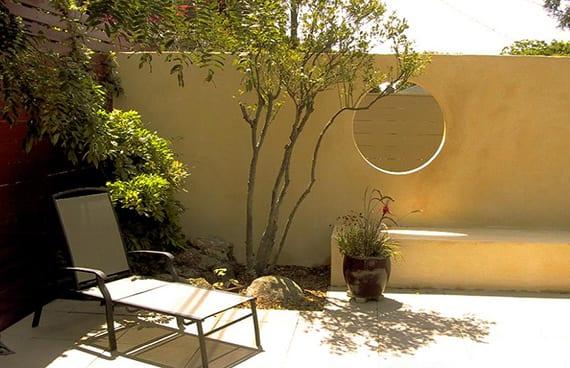 elegante gartengestaltung mit gartenmauer in naturfarbe, rundem fenster und ausgemauerter Sitzbank