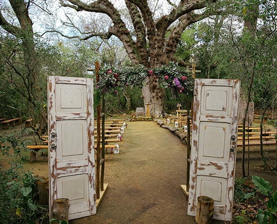 ein offener Platz im wald für die Trauezeremonie ausstatten mit holzbänken und einfachem Eingang aus alten Türen und frischen Blumen