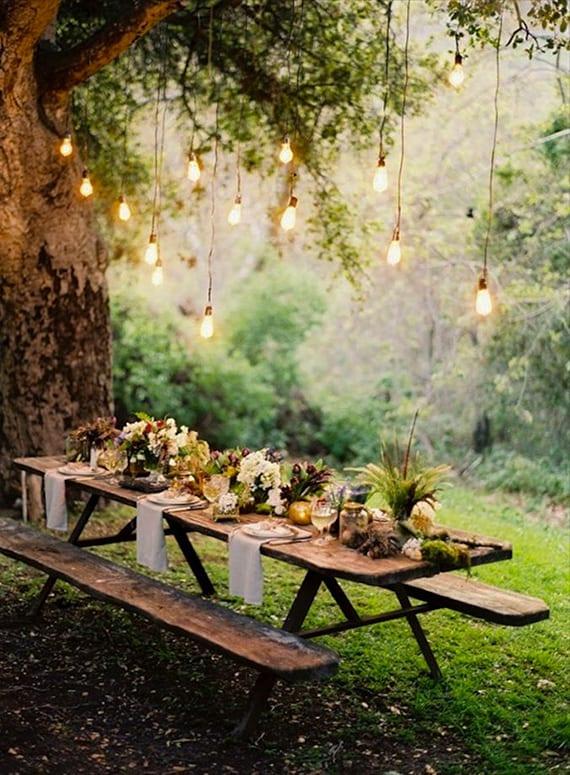 eine waldhochzeit entsprechend beleuchten mit hängenden glühbirnen über dem esstisch