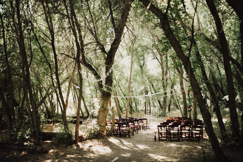 traumhochzeit feiern mitten im Wald_traualtar gestalten mit klappstühlen und weißen girlanden