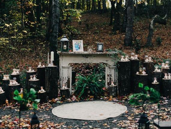 Traualtar im Wald gestalten mit baumstämmen, kerzen und rundem teppich vor dekorativem Kaminmantel aus holz