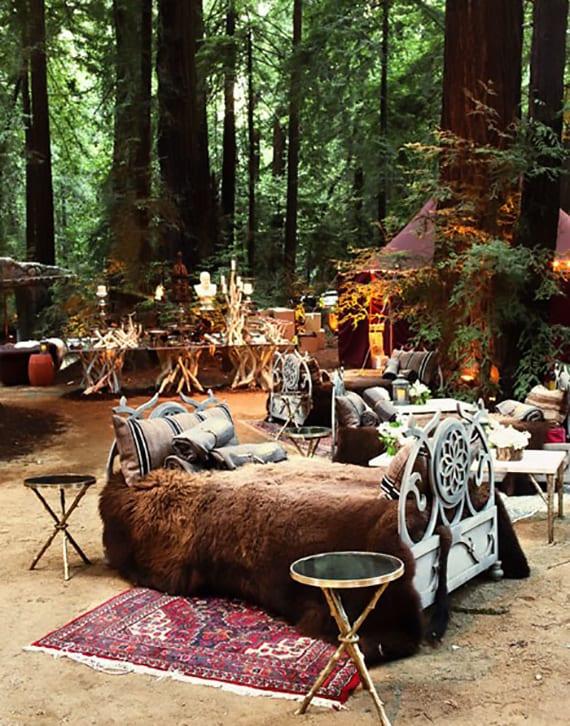 die location einer waldhochzeit mit bequemer sitzgelegenheit wie sofas mit kissen und decken ausstatten