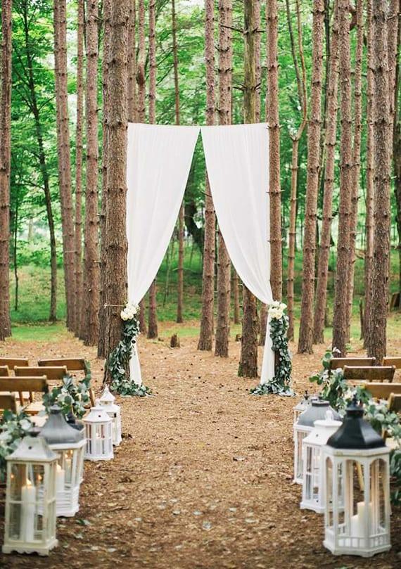 schlichte waldhochzeit dekoidee mit weißen metalllaternen und weißen gardinen für den altar