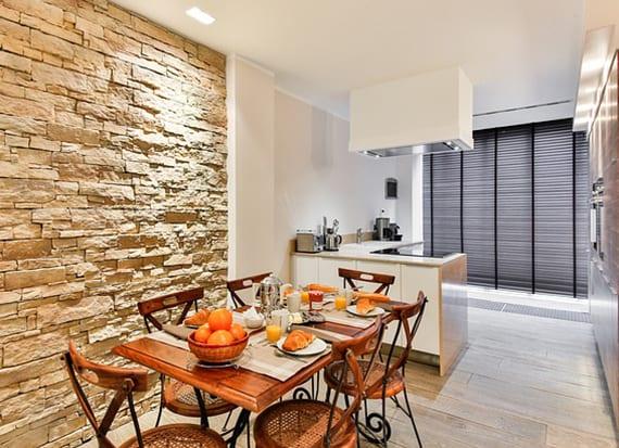 kleine moderne eckküche mit  decken dunstabzug, in der wand eingebautem Kühlschrank und essbereich mit naturstein wandverkleidung und vintage esstisch mit holzstühlen