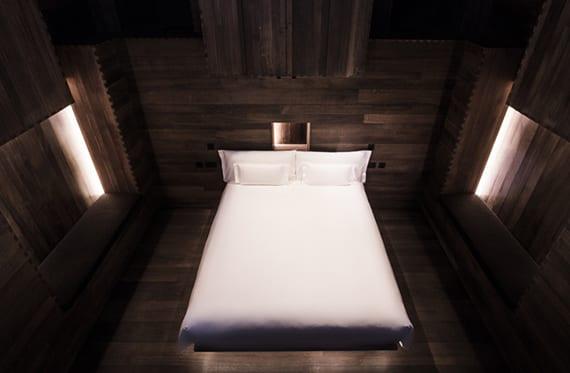 außergewöhnliche Hotelzimmer ohne fenster, mit holzverkleidung und indirekt beleuchteten wandnischen