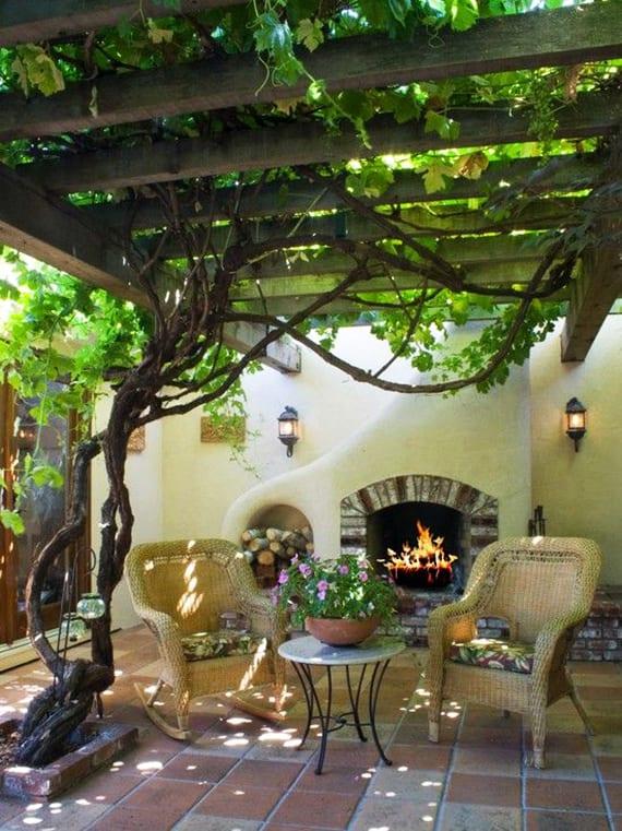 romantische sitzplätze im garten unter einer Weinlaube einrichten mit gartenkamin und schaukelstühlen aus rattan