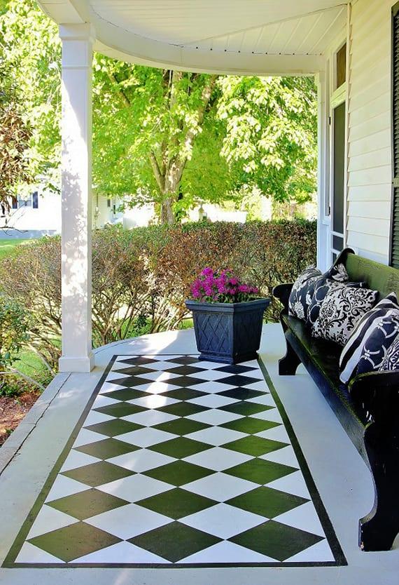coole bodengestaltung einer betonterrasse mit Schachbrettmuster_kleine überdachte terrasse gestalten in schwarz und weiß mit alter holzsitzbank schwarz und schwarzer blumenkübel