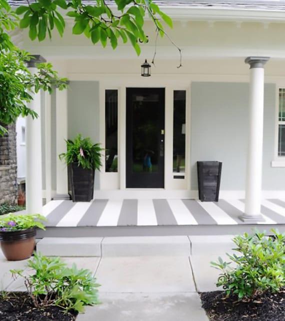 haus mit veranda aus holz und runden säulen modern streichen in grau und weiß