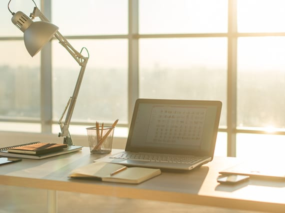 helles und modernes home office einrichten mit holzschreibtisch vor dem fenster und moderner Tischlampe aus metall