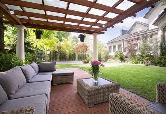 gemütliche sitzecke im garten gestalten mit Gartenmöbeln aus Rattan auf überdachter Holozterrasse mit Holzpergola und antiken Säulen