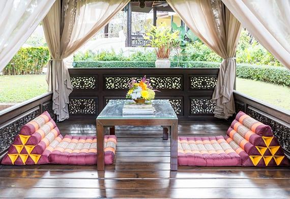 holzpavillion im garten mit Gardinen in Beige, Holzcouchtisch mit glasplatte und bunten Sitzkissen in lila als coole gartenidee für romantische gartensitzecke