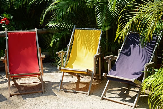 garten gemütlich und fröhlich gestalten mit Gartenmöbeln aus holz in knalligen farben als akzent zu dem Gartengrün