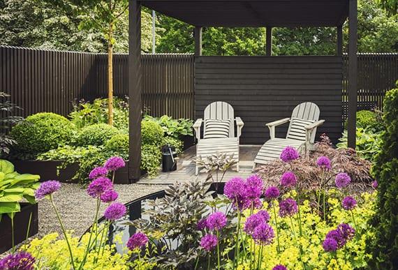 traumgarten gestalten mit wasser, lilafarbigen blumen und Grün in schwarzen metall-hochbeeten und holzpergola