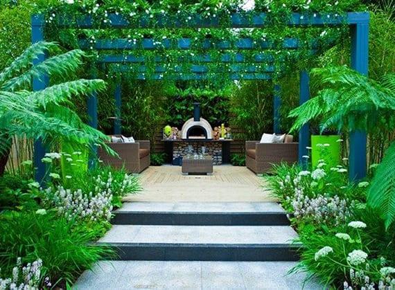 romantische sitzecke im garten mit außenkamin unter holzpergola blau mit weiß blühenden kletterpflanzen