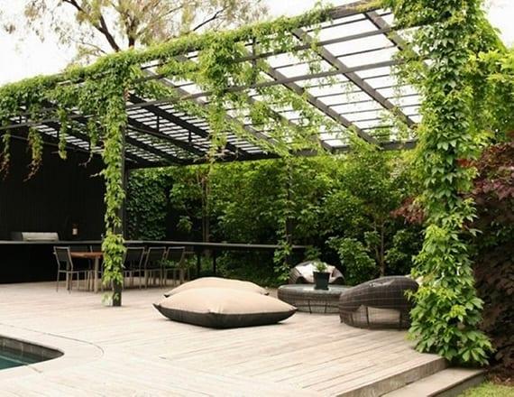 modernes pergola design für grüne überdachung einer holzterrasse mit pool und lounge-möbeln