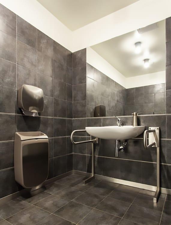 rollstuhlgerechtes Badezimmer austatten mit unterfahrbarem barrierfreiem Waschbecken und Stützhilfen