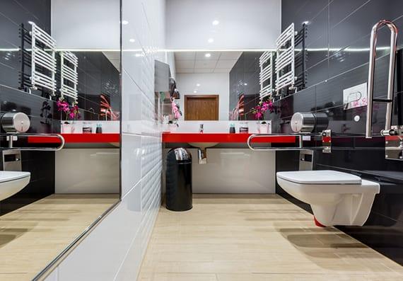 moderne barrierfreie badgestaltung mit großem wandspigel, rutschfestem badfliesen, unterfahrbarem Waschtisch rot und modernen wandfliesen schwarz und weiß