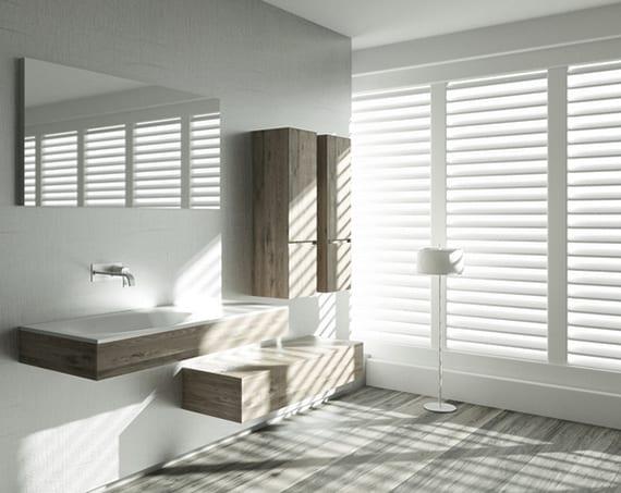 badideen für ein modernes und barrierefreies badezimmer mit modernen Holzbadmöbeln, grauem Bodenbelag in Holzoptik und weißen fenster jalousien