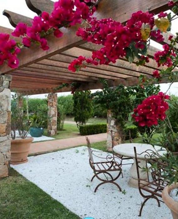 mediterrane gartengestaltung mit holzpergola auf steinstützen, zyklamfarbiger Bougainvillea und metall-Gartenstühlen auf Kiesboden