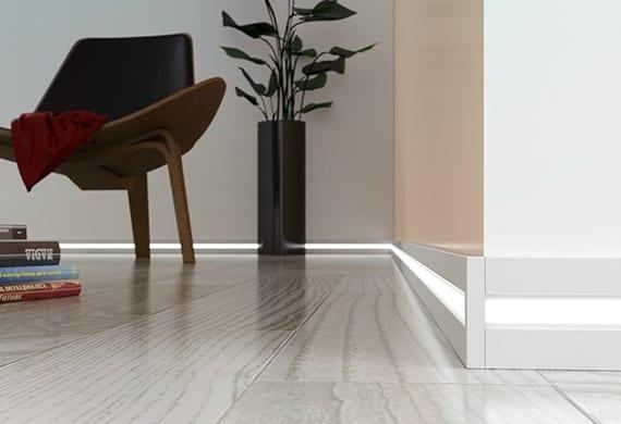 moderne Gestaltungsidee in weiß mit weißgrauer Holzdiele, weißen wänden, LED Sockelleiste weiß, modernem Holzsessel mit schwarzem leder und runder Glasvase schwarz