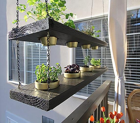 balkon idee mit hängendem Kräutergarten aus schwarzen holzbrettern, ketten und goldenen blumentöpfen