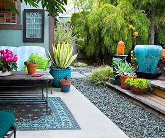 garten idee für wohnliche gartengestaltung im blau mit kies, holzterrasse, rustikale sitzecke mit teppich, sofa und großen blumentöpfen blau