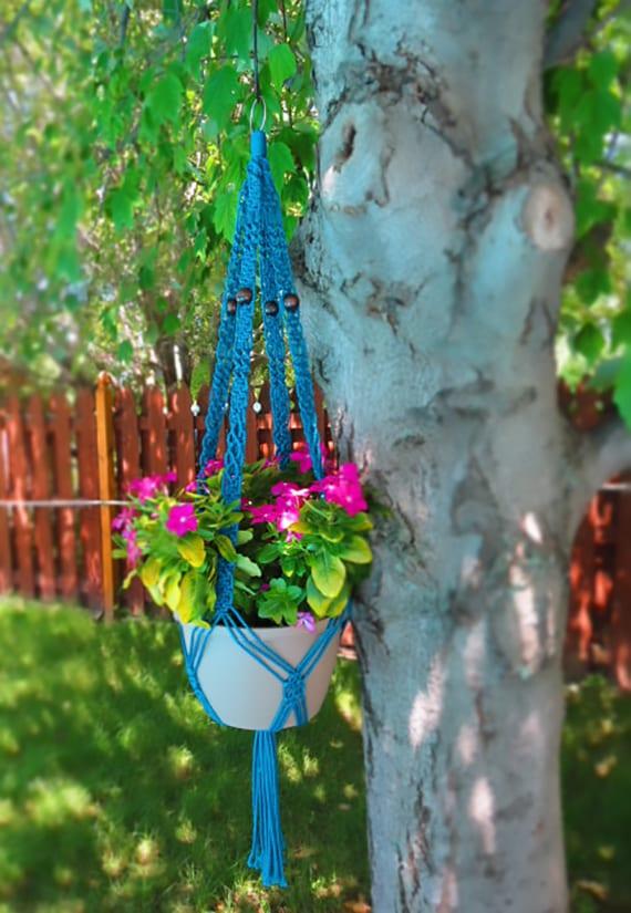 coole gartendeko mit zyklamfarbenen blumen in blauer Makremee pflanzen aufhänger