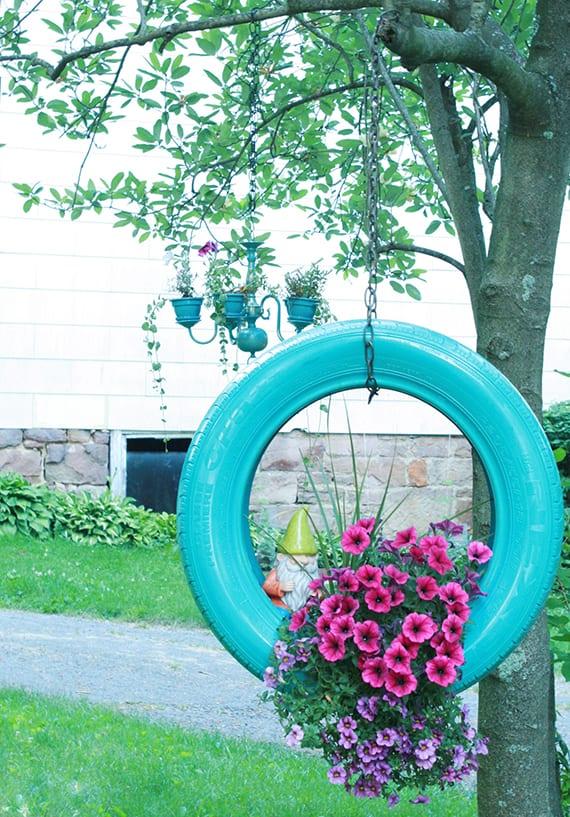 garten dekorieren mit hängenden Balkonpflanzen und Gartenzwerg in blauer Autoreife