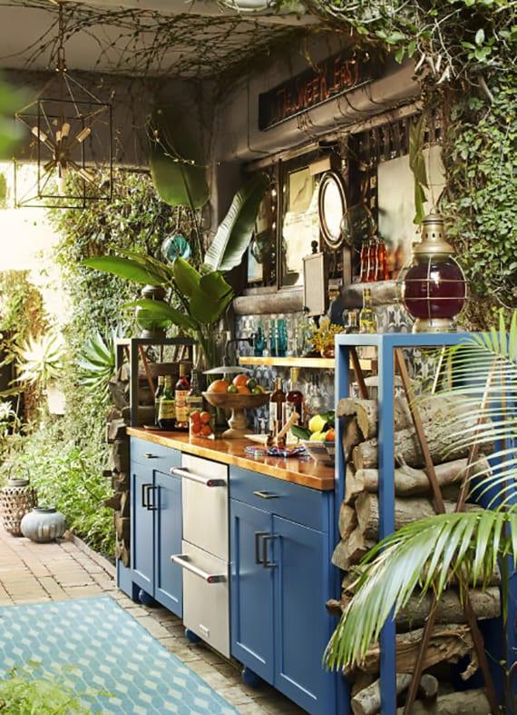 coole gestaltungsidee hofgarten mit grünen kletterpflanzen, überdachte Sommerküche in blau mit mosaik-spritzwand, vintage-pendellampe aus metall, rustikalen laternen und Brennholzregalen blau