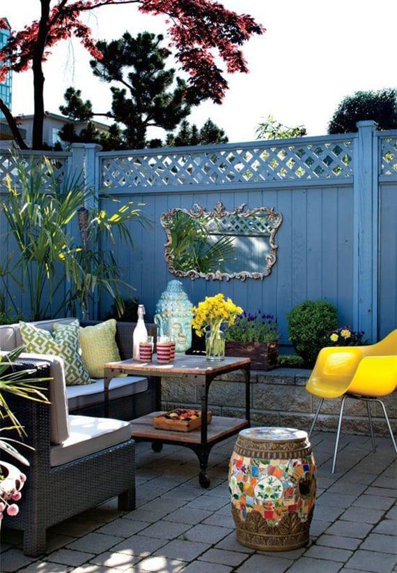 garten entspannend gestalten mit blauer Gartenwand Holz, Spiegel im Silberrahmen, rattangartensofa grau, diy Vintage-Couchtisch auf Rollen und gelbem Stuhl
