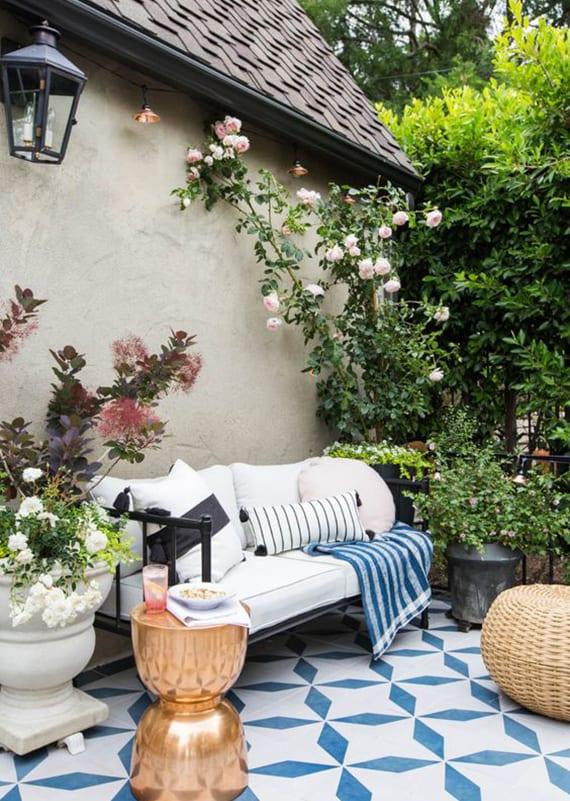 terrasse wohnlich einrichten mit schwarzem sofa aus metall, weißen Polsterkissen, rundem beistelltisch kupfer und weißem teppich mit blauem muster