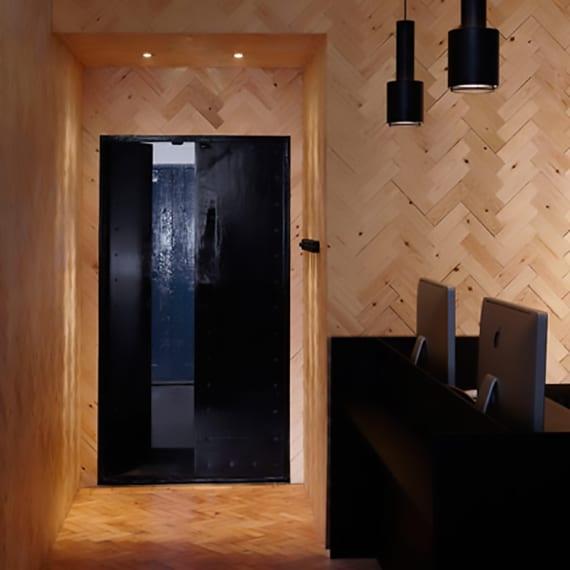 boden und wände im Büro schick gestalten mit parkett_coole Raumgestaltung mit holz, schwarzen Pendellampen, schwarzem Bürotisch und schwarzer Doppelflügeltür